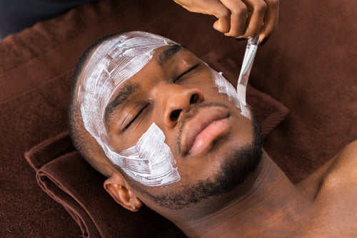 therapist applying facial mask to man