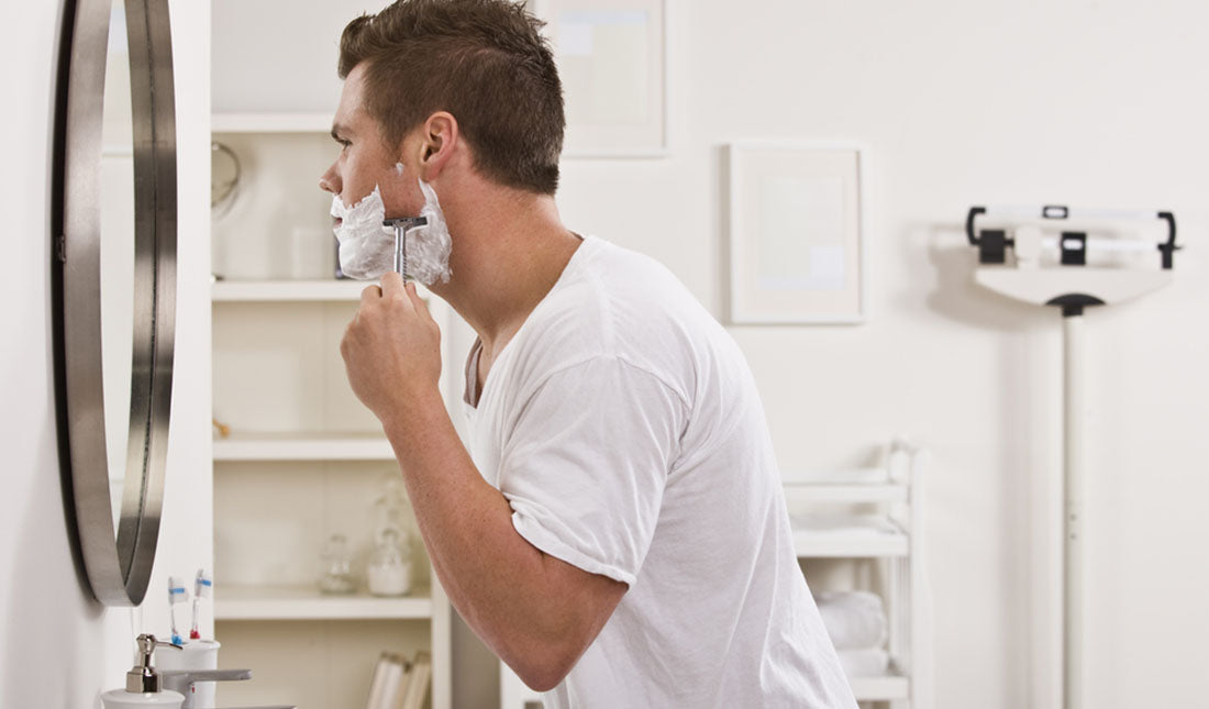 man shaving face before mirror
