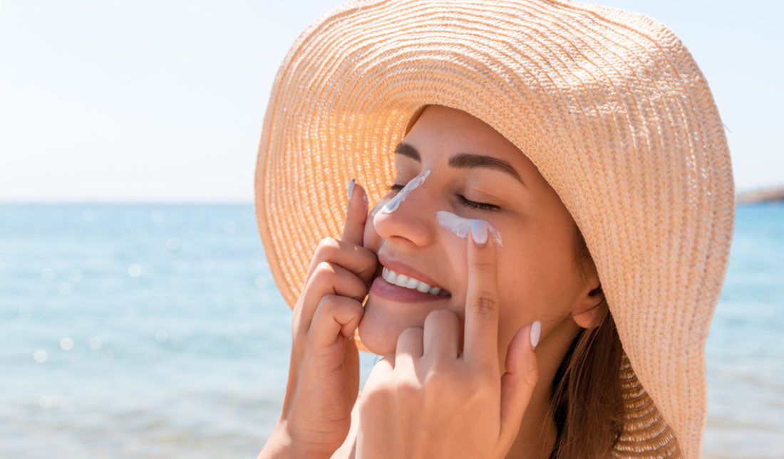 woman applying sunscreen under eyes