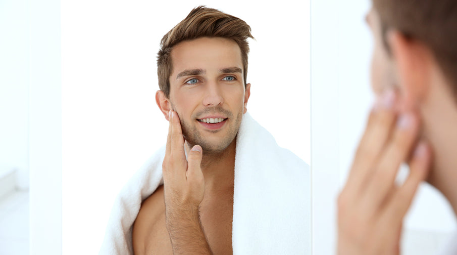 young man touching face in front of mirror