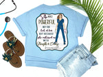 Southern Nurse Tees - living life in scrubs - shirts with sayings - she was powerful not for lack of fear but because she continued on with strength and courage - nurse holding n95 mask - superhero nurse t-shirt - covid 19 coronavirus covid corona tee - inspirational preppy top - cute brunette LPN RN - simply a blue graphic tee