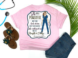 Southern Nurse Tees - living life in scrubs - shirts with sayings - she was powerful not for lack of fear but because she continued on with strength and courage - nurse holding n95 mask - superhero nurse t-shirt - covid 19 coronavirus covid corona tee - inspirational preppy top - cute brunette LPN RN - simply a pink graphic tee