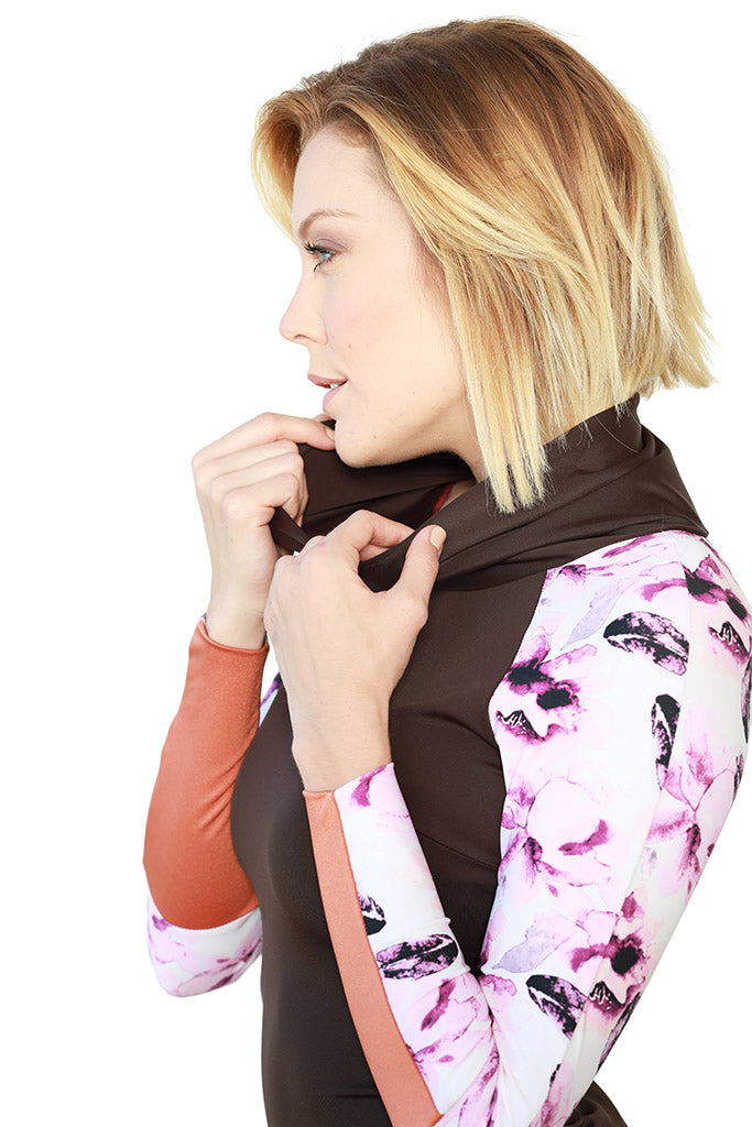blonde wearing brown and floral print iaera surf rash guard