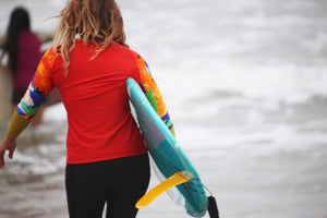 woman holds blue surfboard wears red iaera surf rash guard