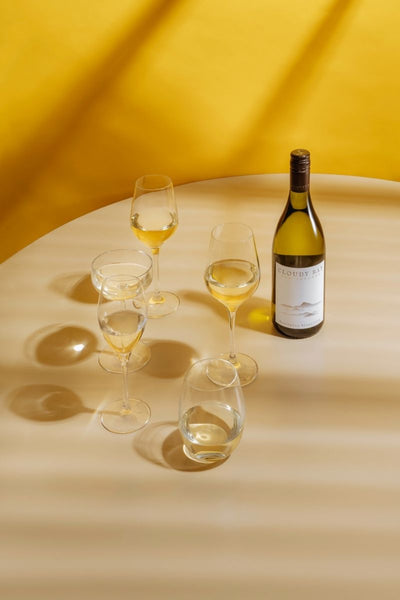 cloudy bay white wine bottle and glasses with yellow background