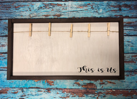 This is us custom wooden sign intended to hold photo with clothespins.  Comes with 5 pins, but could hold more.