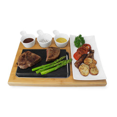 hot cooking platter with steak, asparagus, sauces and garnish