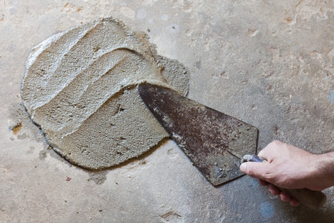 OnFloor smoothing out wet concrete with trowel