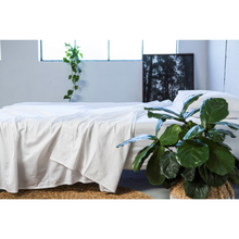 white-bed-sheet-with-plants-and-balck-and-white-painting