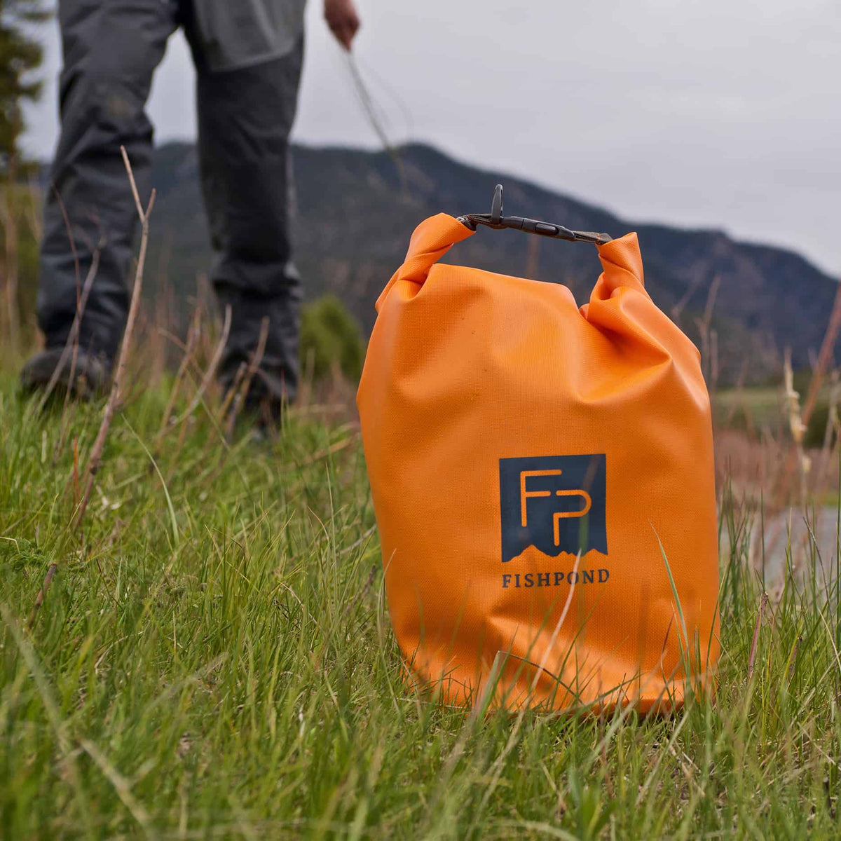 Fishpond Thunderhead Roll Top Dry Bag Cutthroat Orange On Bank With Person