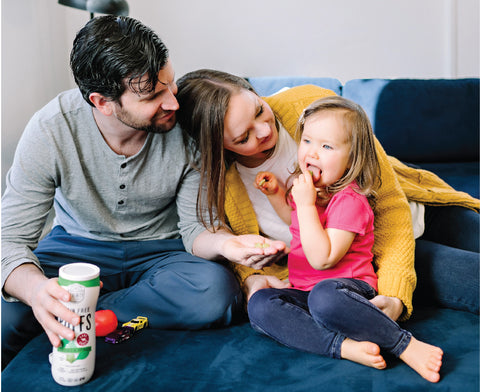 Serenity Kids - Co-Founders Serenity & Joe Carr with their daughter Della eating Grain Free Puffs