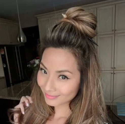 A brunette woman wears a Tidal Hair Stick to hold up her topknot hairstyle.