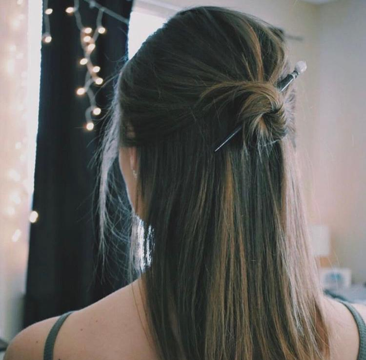 A brunette Millennial wears a Tidal Hair Stick in her topknot bun.
