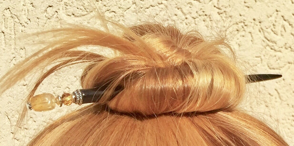 This is a close-up picture of a blonde hair bun held up by just one Tidal Hair Stick, no elastic band at all.