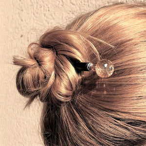 A blonde woman wearing the Abigail Hair Stick in her messy updo.