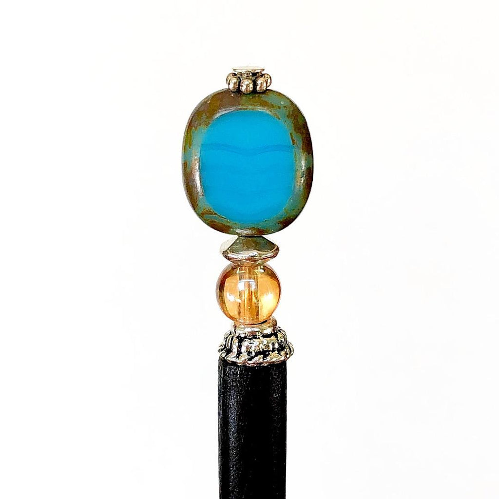 A close up of the Adelaide Tidal Hair Stick made of a blue Czech glass bead and wood base.