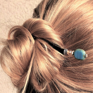 A blonde woman wearing the Adelaide Tidal Hair Stick to secure her messy hairbun.