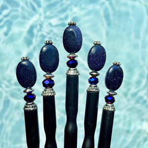 Five Andromeda Tidal Hair Sticks made from blue goldstone.