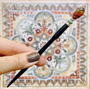 A hand holding the Bree Tidal Hair Stick made from a teardrop Jasper bead.