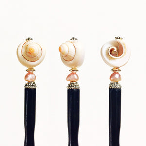 Three different close up views of the Cali Tidal Hair Stick made from a natural shell bead and pearl accent bead