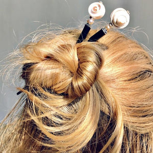 A blond woman wears a messy bun using two of the the Cali Tidal Hair Stick made from a natural shell bead and pearl accent bead