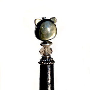 A close up of our Kat Hair Stick made from a black mother of pearl bead shaped like a cat head.