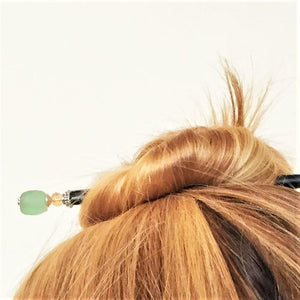 A blonde woman wearing the Daliah Hair Stick made from aqua African Recycled Glass beads.