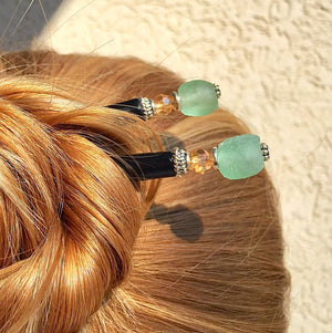 A blonde hair bun is secured by two of the Daliah Hair Stick made from aqua African Recycled Glass beads.