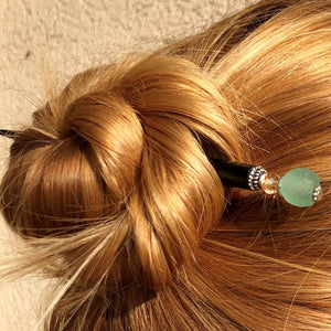 A blonde woman wears a hairbun using the Daliah Hair Stick made from aqua African Recycled Glass beads.