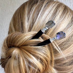 A blonde woman wearing two Labradorite Hair Sticks in her hair bun