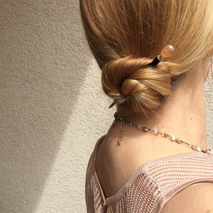 A blonde woman wears a low bun secured with the Ellen Hair Stick made from blush pink peach African Recycled Glass beads.