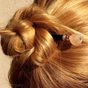 A blonde woman wears a hair bun with the Ellen Hair Stick made from blush pink peach African Recycled Glass beads.