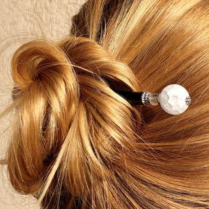 A blonde woman wears a messy bun by using the Elodie Hair Stick made from frosted white crackle quartzite beads.