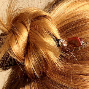 A blonde woman wears a messy bun with the Eve Tidal Hair Stick made from pink mother of pearl shell beads.