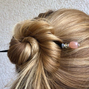 A woman wearing one of our Farah Hair Sticks made from peach moonstone.