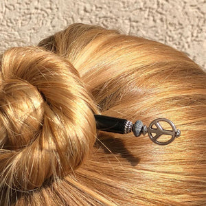A blonde woman weras a hair bun using the Freedom Tidal Hair Stick made from a silver peace sign and denim-colored accent bead.