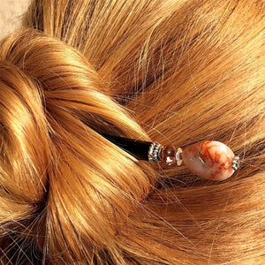 A blonde woman wearing a messy bun using the Gemma Tidal Hair Stick made from Bamboo Agate Stone beads.