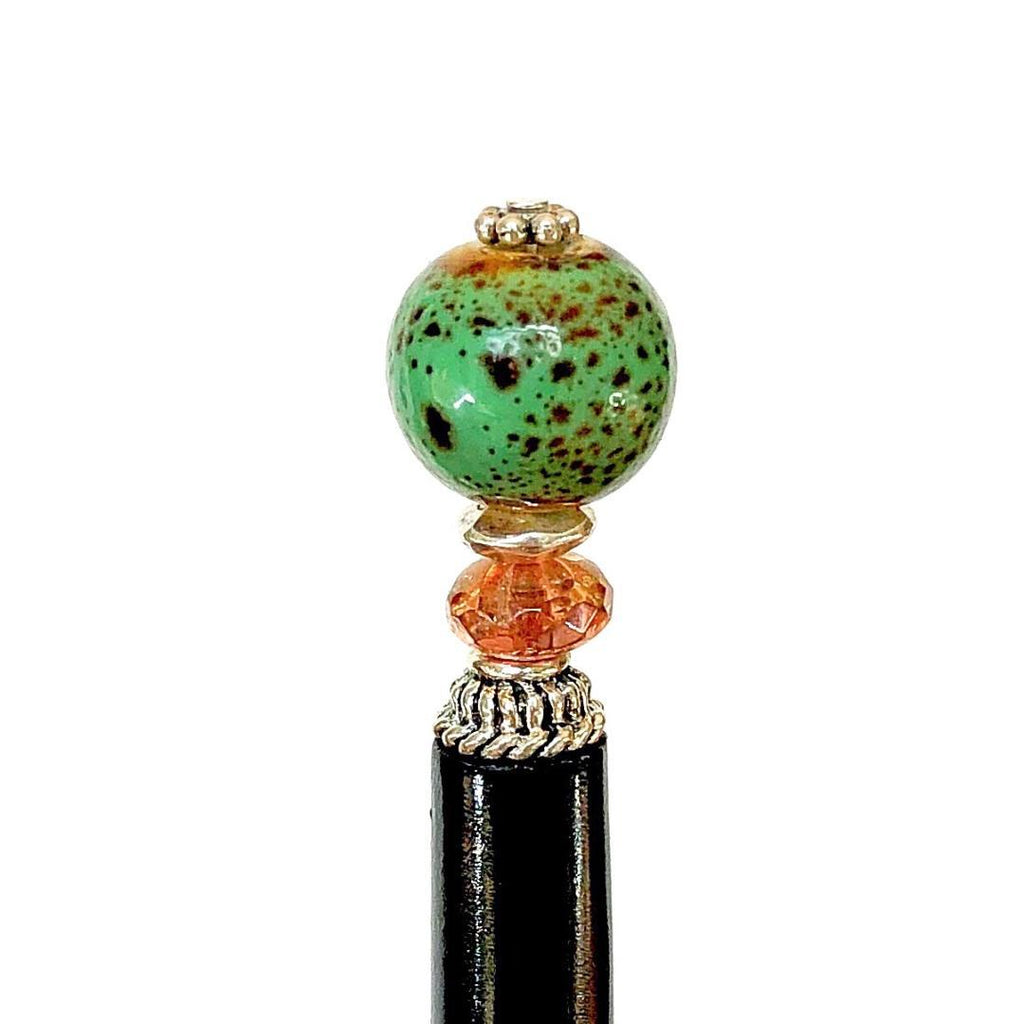 A close up of the Harlow Tidal Hair Stick made from green raku fired ceramic beads.