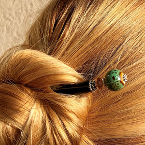 A blonde woman wears a hairbun using the Harlow Tidal Hair Stick made from green raku fired ceramic beads.