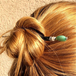 A woman wears a hair bun using the Joanna Tidal Hair Stick made from aqua green aventurine stone beads