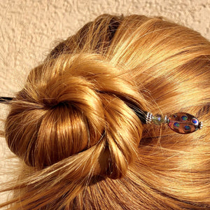 A blonde woman wears a messy bun using one of the Juno Tidal Hair Sticks made from purple Czech glass beads.