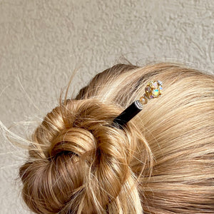 A woman wearing a Kathleen Hair Stick made from a gold Czech glass bead