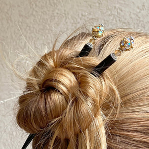 A woman wearing two of the Kathleen Hair Sticks made from gold Czech glass beads