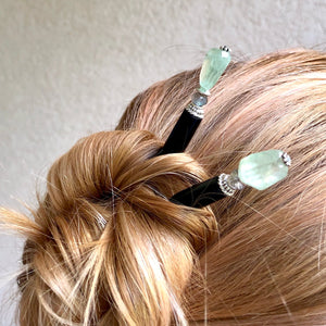 A woman wears two of the Kira Tidal Hair Sticks made from green fluorite stones.
