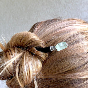 A woman wears one of the Kira Tidal Hair Sticks made from green fluorite stones.