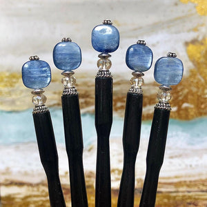 Five of the Kya Tidal Hair Sticks made from blue luster Kyanite stones.