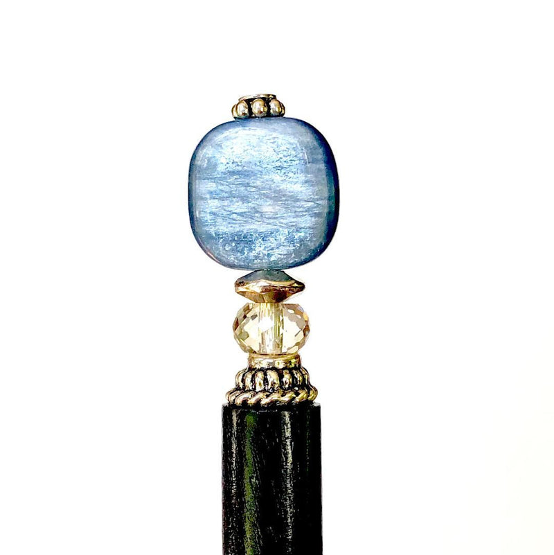 A close up of the Kya Tidal Hair Stick made from blue luster Kyanite stones.