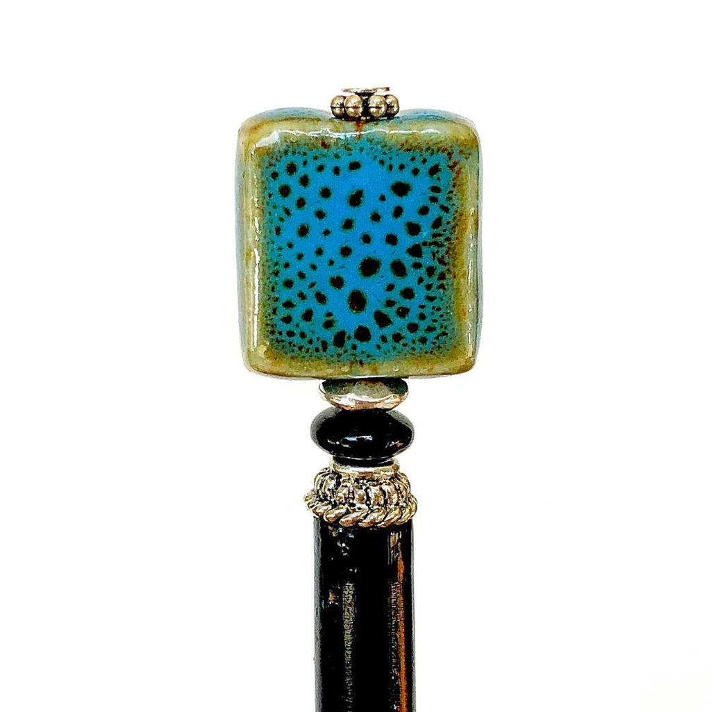 A close up of the Lark Tidal Hair Stick made from square blue raku fired ceramic beads.