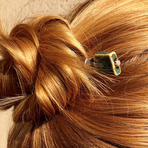 A blonde woman wears a messy bun using the Lark Tidal Hair Stick made from square blue raku fired ceramic beads.