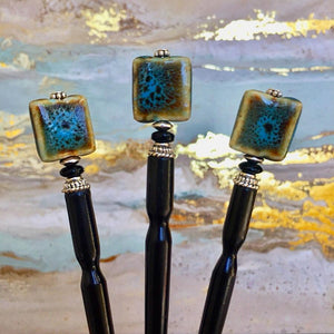 Three of the Lark Tidal Hair Sticks made from square blue raku fired ceramic beads.